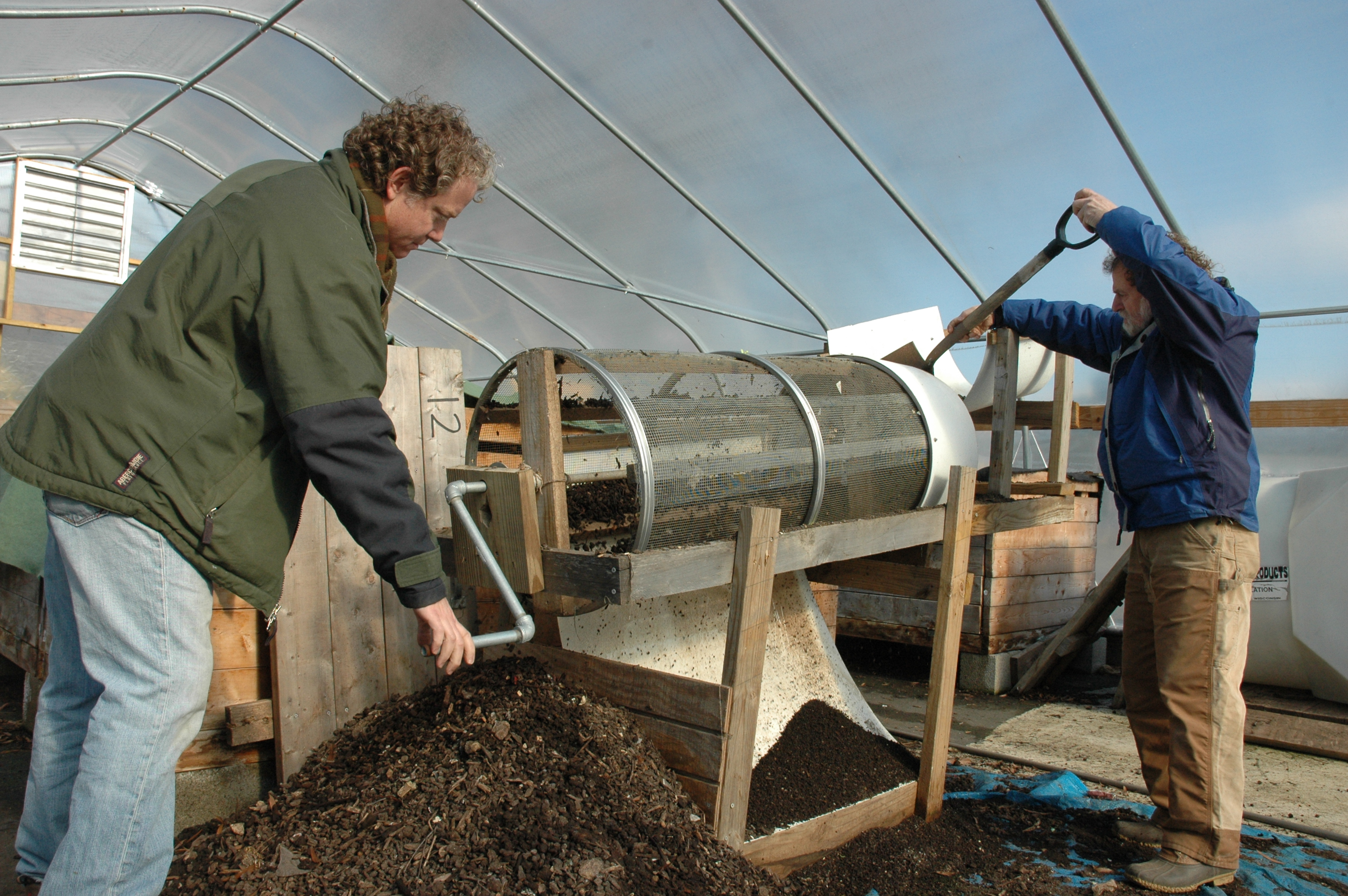 ECO City Farms staffers harvested materials at Community Forklift to build this compost sifter. Here, apprentice Matthew turns the crank, while senior technical adviser Benny Erez, right, shovels compost into the device.