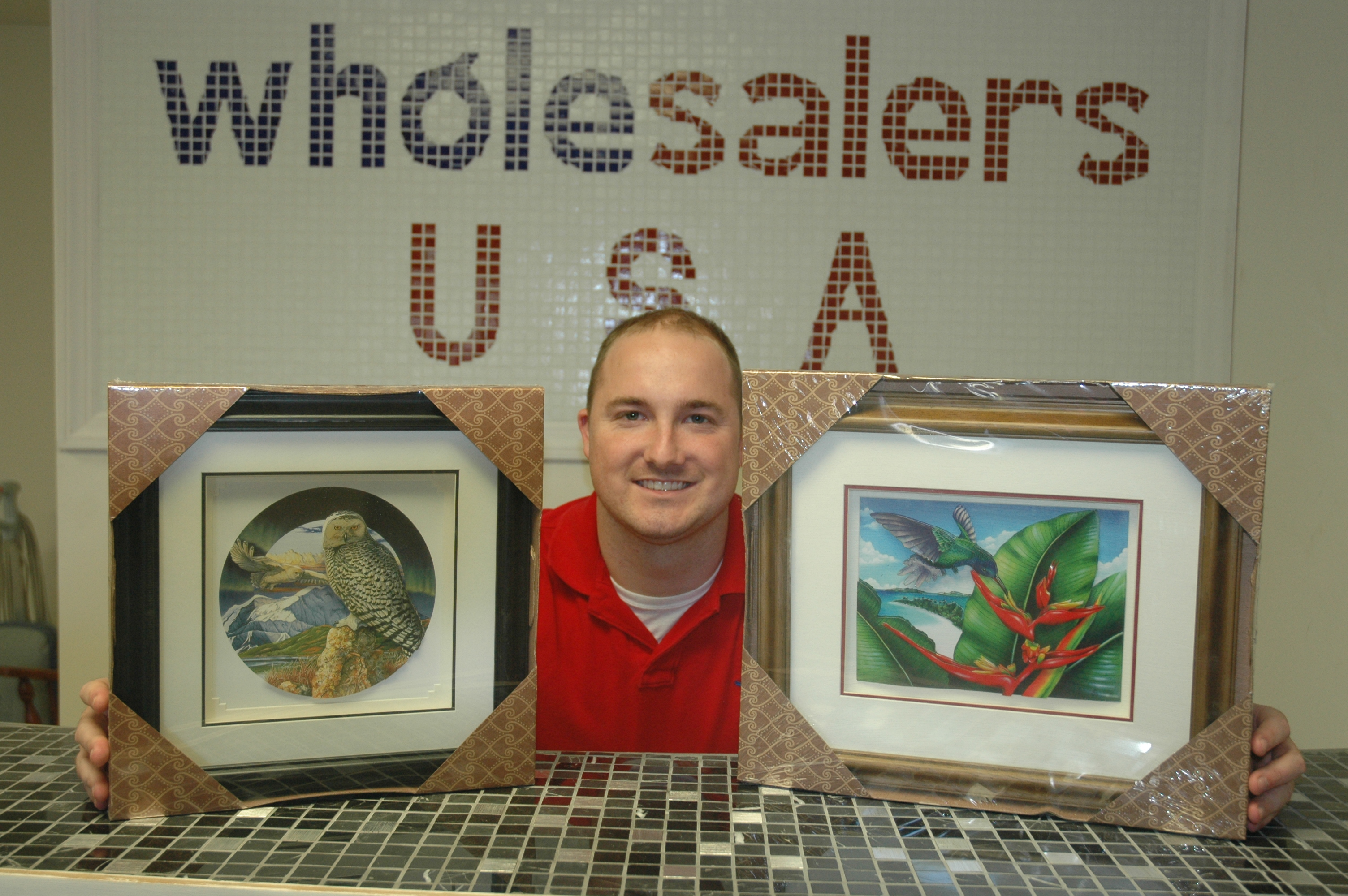 John Gray shows off samples of the handmade shadowbox artwork that Frederick, Md.-based Wholesalers USA Inc. donated to Community Forklift this autumn. Each piece includes an artist's biography.