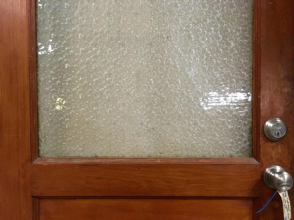 Closeup photo of door with pebbled glass